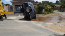 SUV 'swallowed by avenue' after driving into water-stuffed hole
