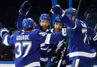 Defending champion Tampa Bay Lightning pile on against Montreal Canadiens in Game 1