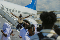 Deported Haitians try to rush back into plane amid anger